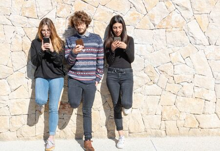 3 people - 1 young man and 2 young women using their mobile phone - Multiracial and multiethnic group - Negative space