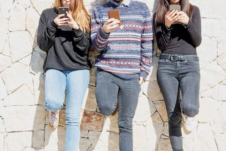 Young people using their smartphone against a wall cut face unidentified person
