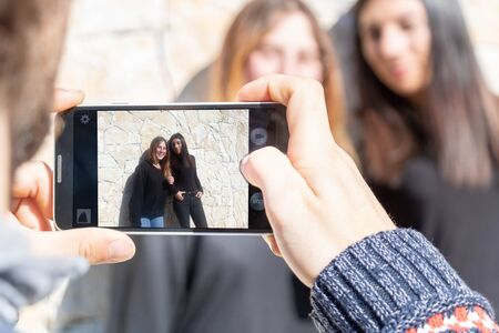 Two young women being photographed with a smartphone - Multiracial Multiethnic Group