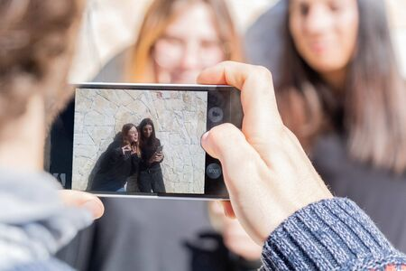 Young man taking a photo with his smartphone his 2 friends - blond woman and brunette woman - multiracial and multi-ethnic group