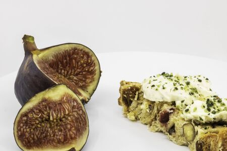 Fresh goat cheese toast with herbs and chopped mustots on a slice of dried fruit and bread with fresh fig - isolated on rustic white background 写真素材