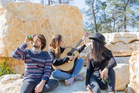 Music Festival Young people having fun with a musician playing guitar during an original picnic in a stone quarry