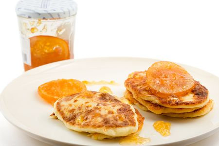 small cottage pancakes with some orange jam, jam jar in background, isolated on white photo