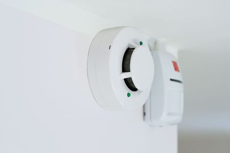 alarm security: smoke detector and alarm mounted on a wall, shallow DOF