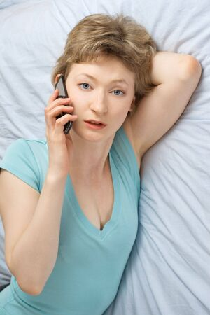 25 30: young woman with mobile phone on a bed, shallow DOF, focus on eyes
