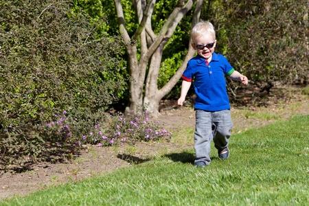 toddler walking: happy toddler walking on the grass