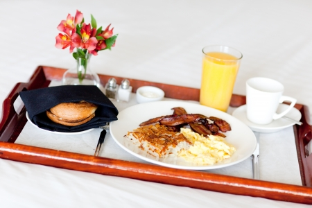 breakfast hotel: delicious breakfast served on the tray on the hotel room bed Stock Photo