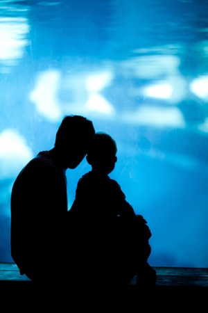 silhouettes of father and son looking in the aquarium photo