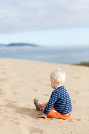 thoughtful toddler sitting alone on the beach photo