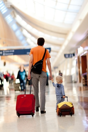 departure board: father and son with the luggage in the airport Stock Photo