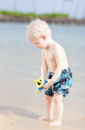 cute toddler using watering pot on a beach photo