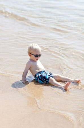 thoughtful caucasian toddler relaxing at the beach photo