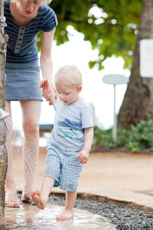 mother helping son to shower feet after beach photo