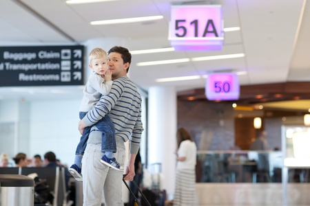 father and son waiting together at the airport photo
