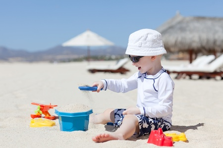 adorable smiling toddler playing at the tropical beach photo