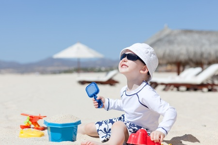 cute toddler enjoying summer vacation at the tropical beach photo