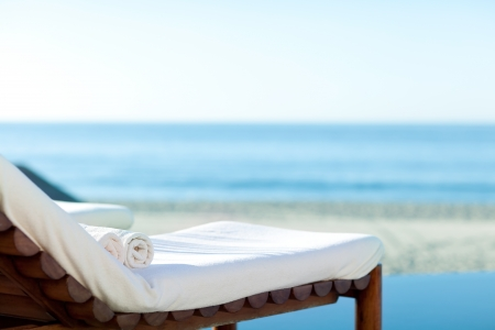 beach towel: empty sunbed with wrapped towels on a beautiful beach Stock Photo