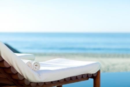 strandlaken: lege zonnebank met verpakte handdoeken op een mooi strand