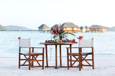 table setting ready for a romantic dinner at the beach photo