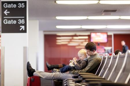gente aeropuerto: padre y su hijo jugando y esperando en el aeropuerto