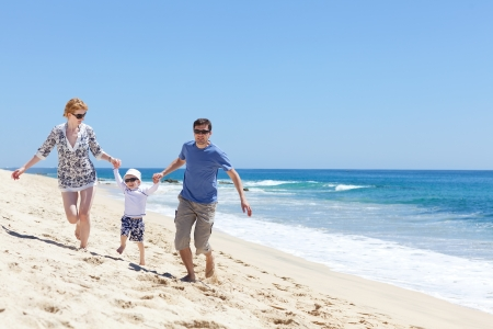 cheerful family of three running at the beach photo