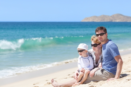 cheerful family of three at the tropical beautiful beach photo