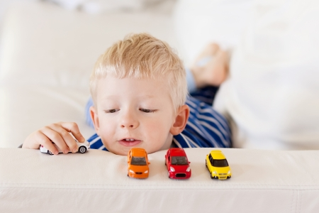 young caucasian boy plays with colorful toy cars photo