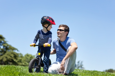 ni�os en bicicleta: sonriente feliz padre con su hijo en una bicicleta equilibrio