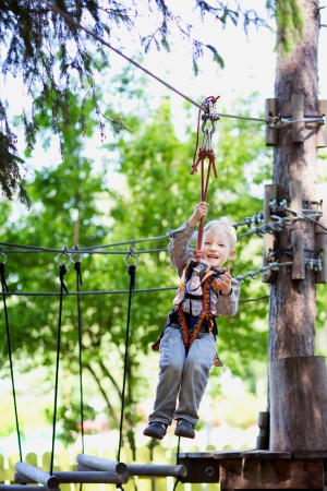 adorable cheerful little boy ziplining in the forest photo