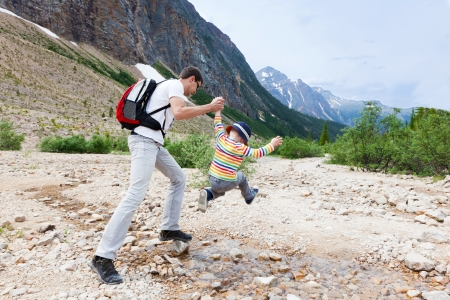 hike: father helping his son to jump over stream in jasper national park