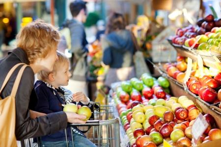 groceries: madre y su hijo comprando frutas en un mercado de agricultores Foto de archivo