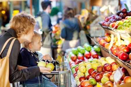 grocery cart: mother and her son buying fruits at a farmers market