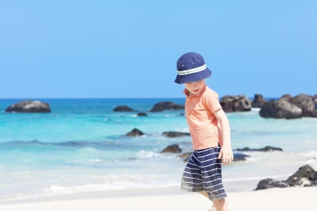 petit gar�on marche sur la plage tropicale photo