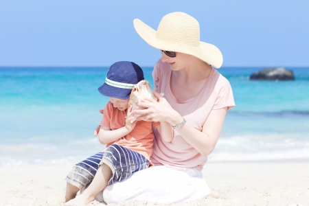 little cute child is listening to a shell with his mother at a tropical beach photo