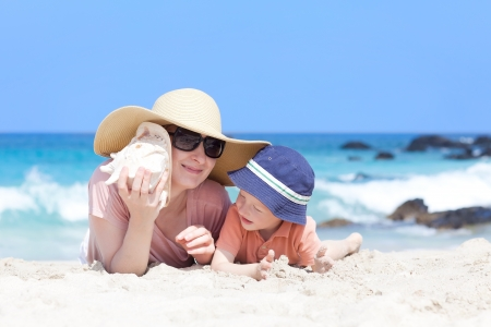 madre est� acostada con su hijo en una playa tropical y escuchando una concha photo