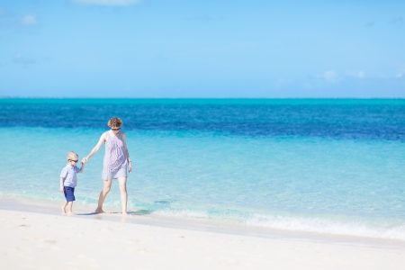 mother and her son strolling at the caribbean beach photo