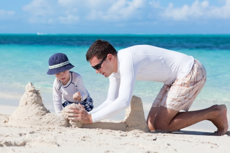 sandcastle: little kid and his father building sandcastle Stock Photo