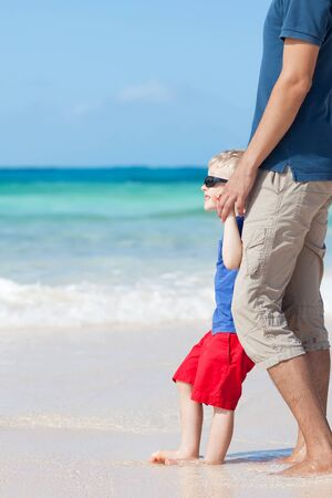 little kid barefoot at the perfect beach with his father photo