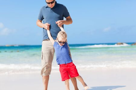 father and his son playing at the caribbean beach photo