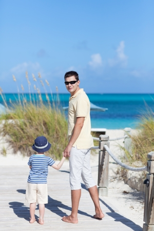 smiling handsome young man with his son at the caribbean beach photo