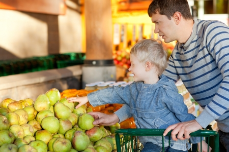 father and his cheerful son choosing fruits at the market photo