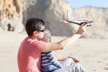 father and his little son playing with toy plane together photo