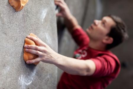 登る: 若い白人男性ロック クライミングの室内