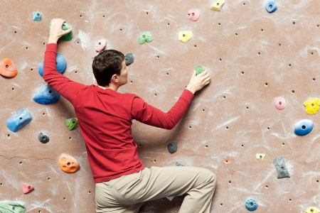 to climb: young caucasian man rock climbing indoors