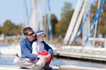 caucasian father and his son sitting at a marina dock together photo