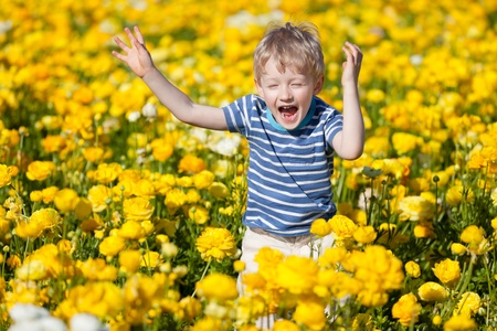 happy smiling kid jumping at the flower field photo