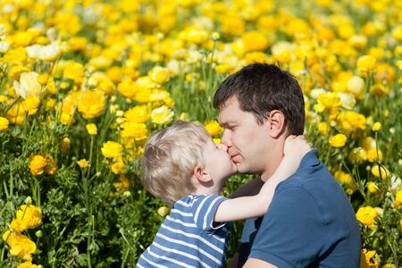 adorable little boy and his father hugging and kissing in the park photo