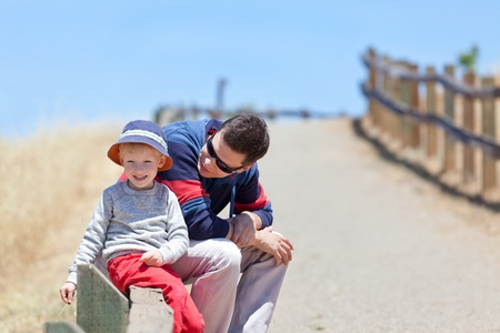 happy family of two spending time together; adorable smiling son enjoying summertime with his father at the park photo