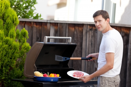 young handsome man ready for grilling meat and vegetables at his house backyard photo