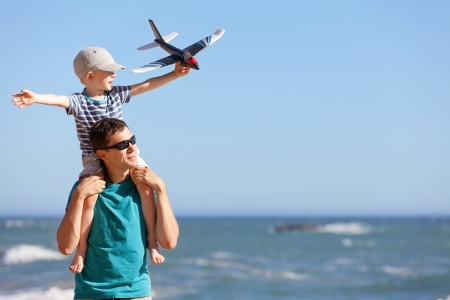 happy adorable boy holding toy plane and sitting on his young handsome father shoulders and having fun together outdoors Stock Photo